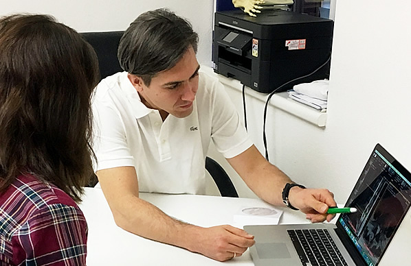 Ordination für Neurochirurgie Dr. Stephan Emich erklärt Patientin Befunde auf Computerbildschirm
